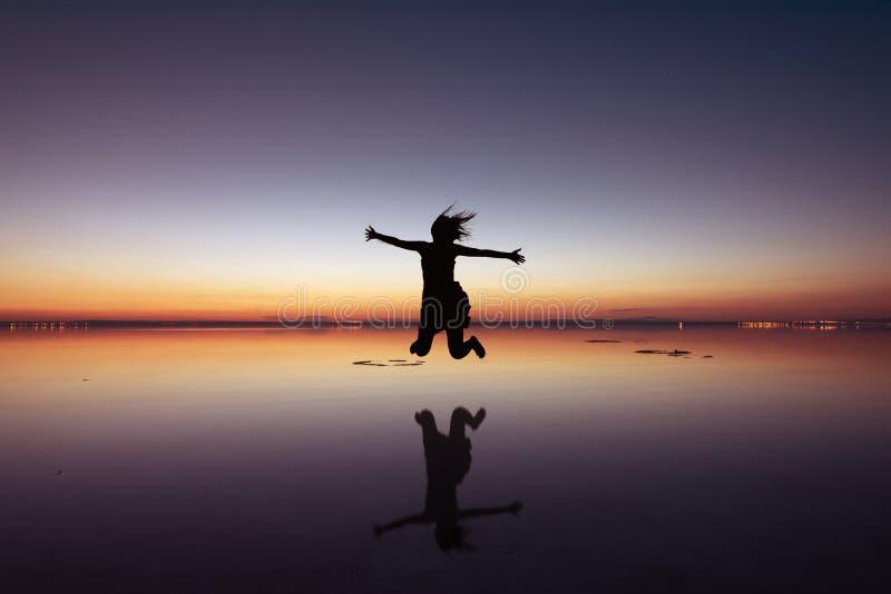 A mulher que salta acima em um ajuste bonito do por do sol foto de stock royalty free