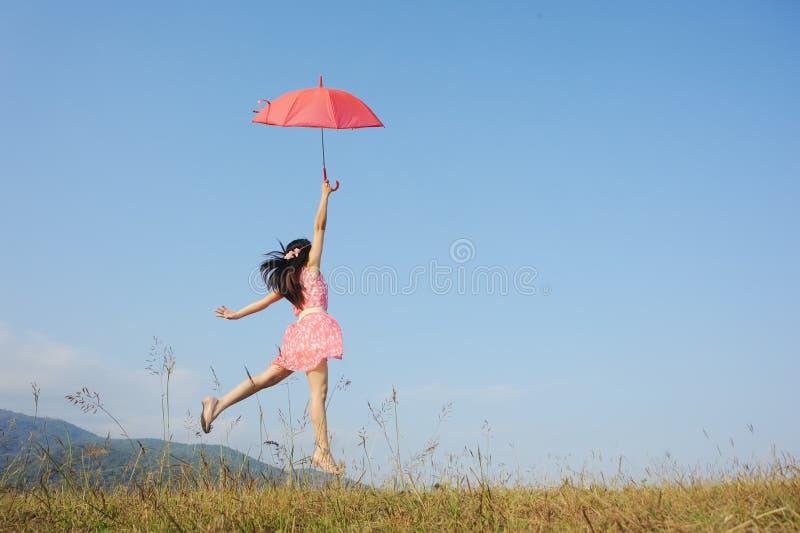 A mulher que salta ao céu azul com guarda-chuva vermelho foto de stock