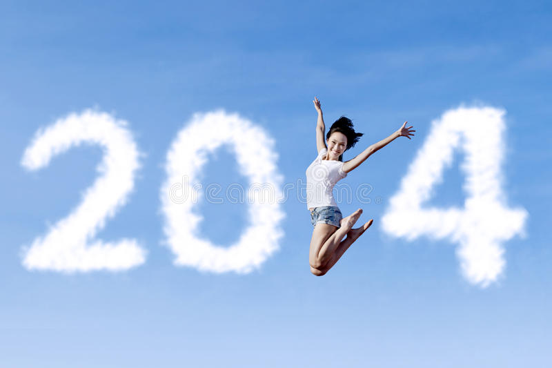 A mulher que salta com ano novo 2014 imagem de stock
