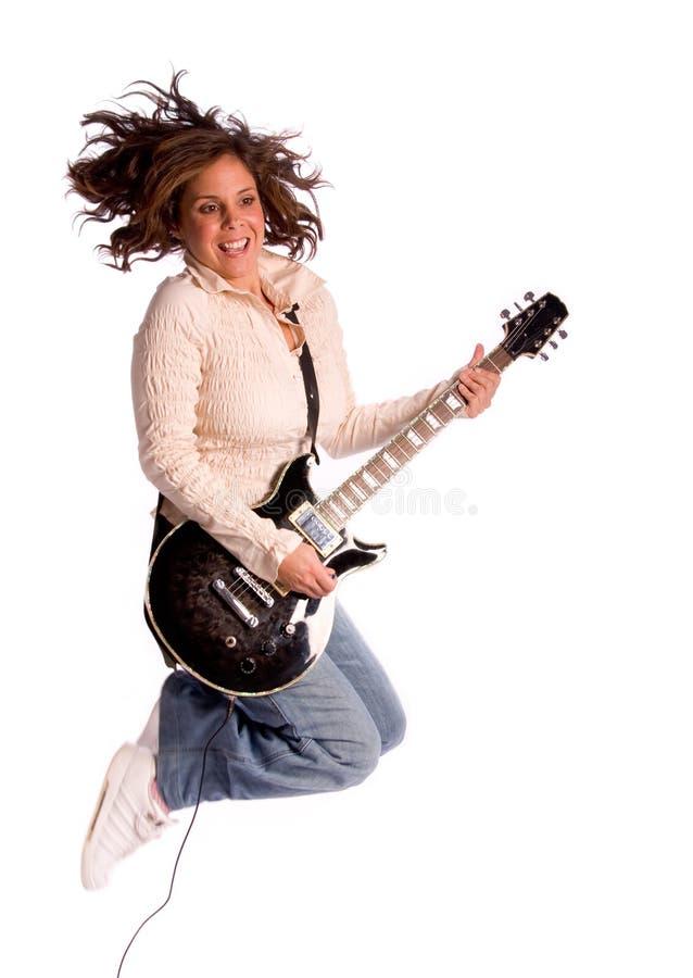 A mulher que salta com guitarra elétrica fotografia de stock royalty free