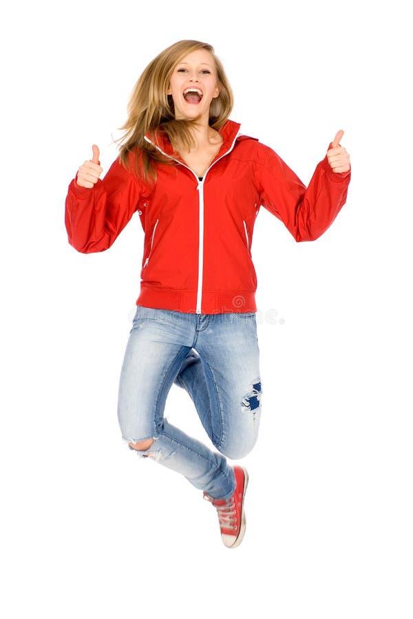 A mulher que salta com polegares acima fotos de stock