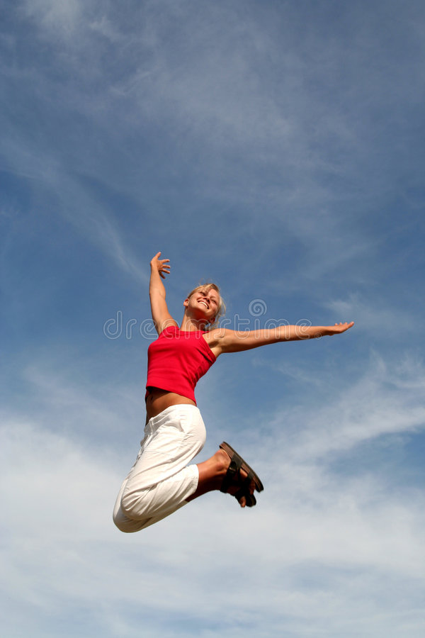 A mulher que salta de encontro ao céu azul imagem de stock