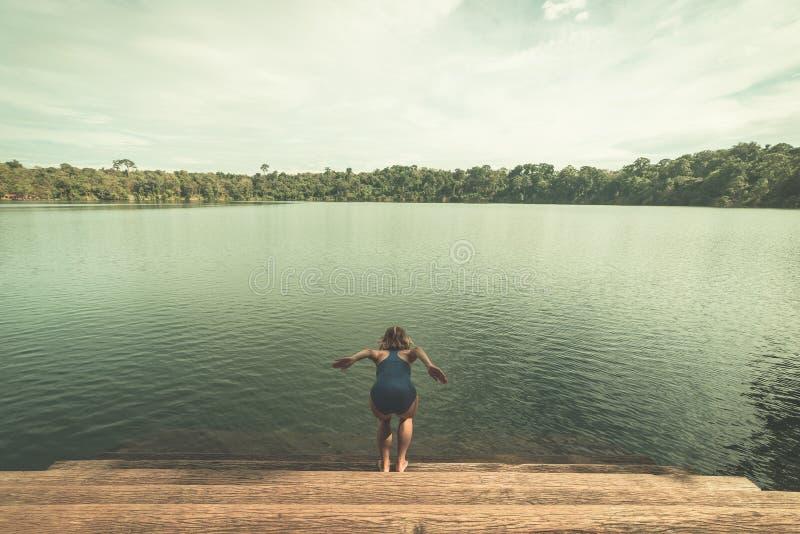 A mulher que salta na água do lago vulcânico cercada pela floresta em Banlung, Camboja, destino do curso Estilo tonificado do vin imagens de stock royalty free