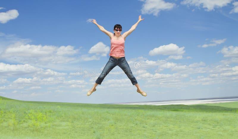 A mulher que salta na grama verde sobre o céu azul foto de stock