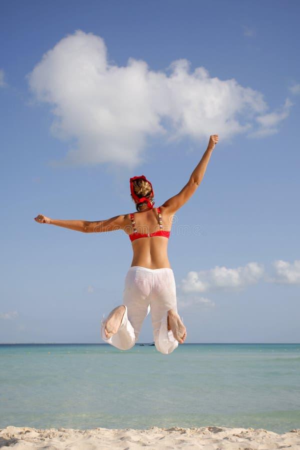 A mulher que salta na praia fotos de stock royalty free