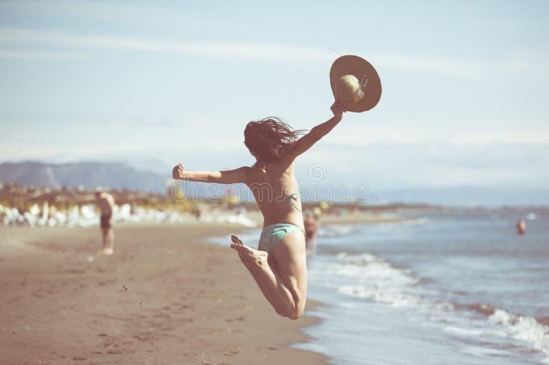 A mulher que salta no ar na praia tropical, tendo o divertimento e comemorando o verão, salto brincalhão bonito da mulher da feli foto de stock