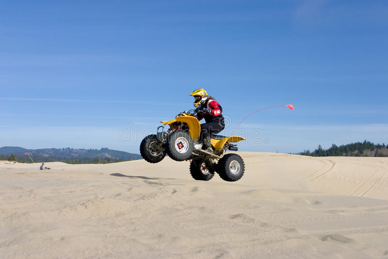 A mulher que salta seu ATV nas dunas fotos de stock royalty free
