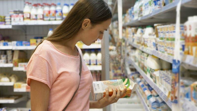Mulher que seleciona o alimento de leiteria no refrigerador no departamento do mantimento do shopping imagens de stock