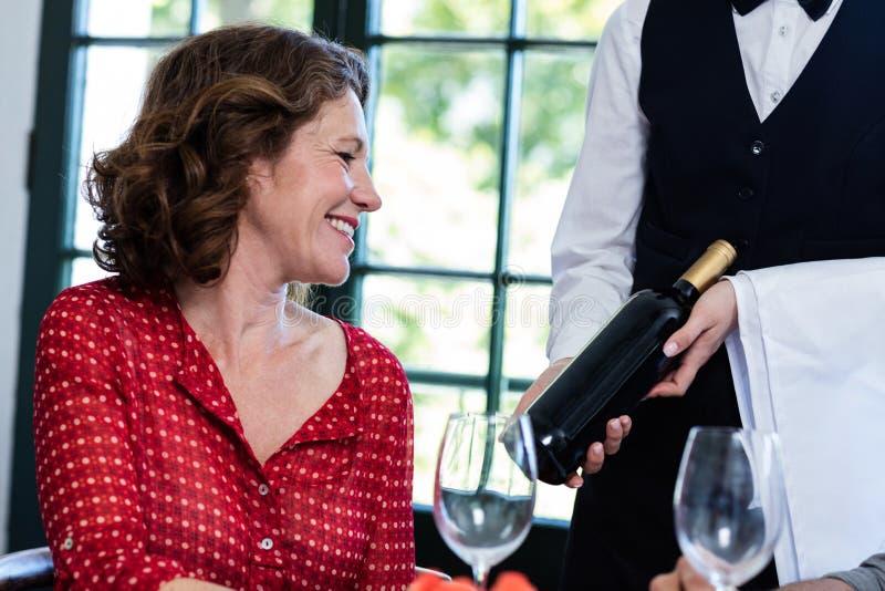 Mulher que seleciona uma garrafa do vinho imagem de stock