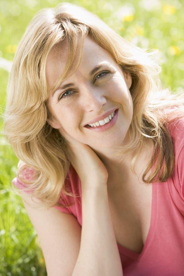 Mulher que senta ao ar livre o sorriso imagens de stock royalty free