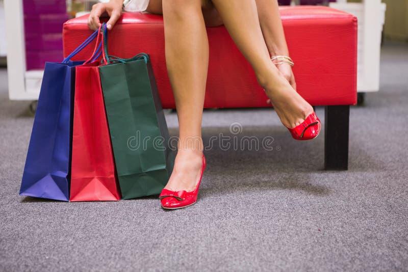 Mulher que senta-se ao lado dos sacos de compras e que põe sobre sapatas fotos de stock royalty free
