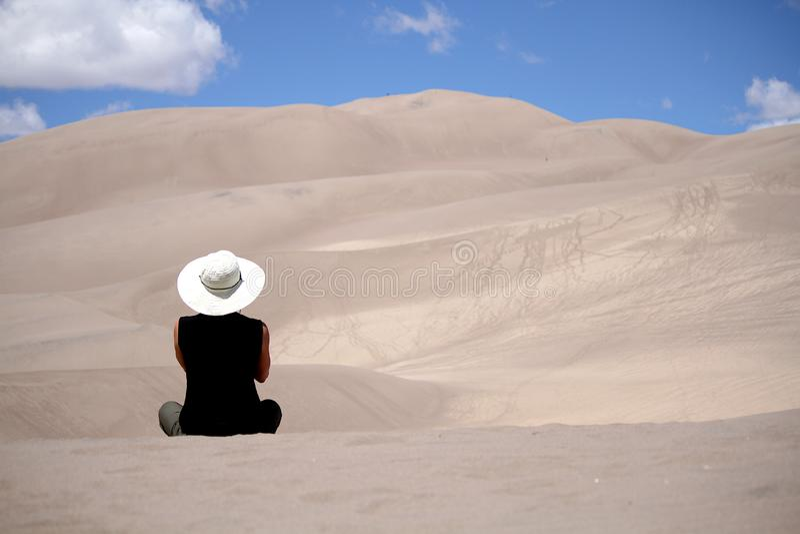 Mulher que senta-se apenas em dunas de areia do deserto foto de stock