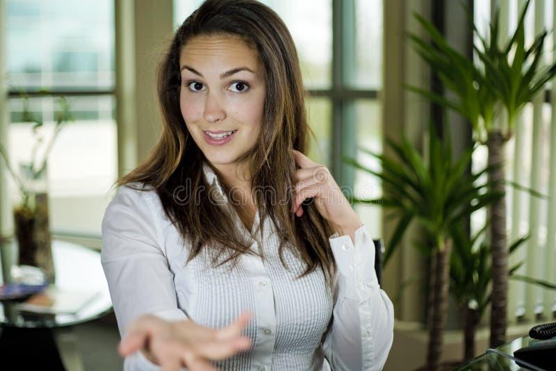Mulher que senta-se atrás de uma mesa imagens de stock