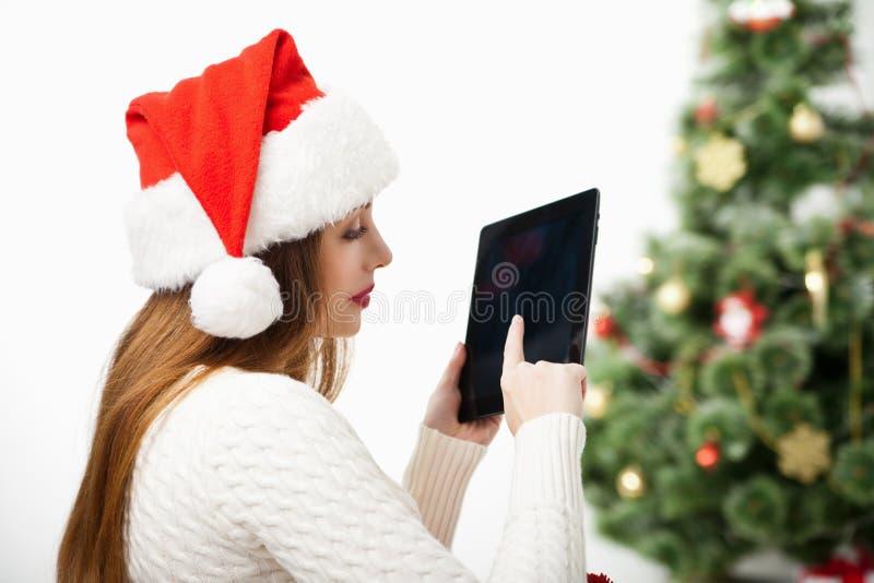 Mulher que senta-se com o PC da tabuleta sobre a árvore de Natal imagem de stock