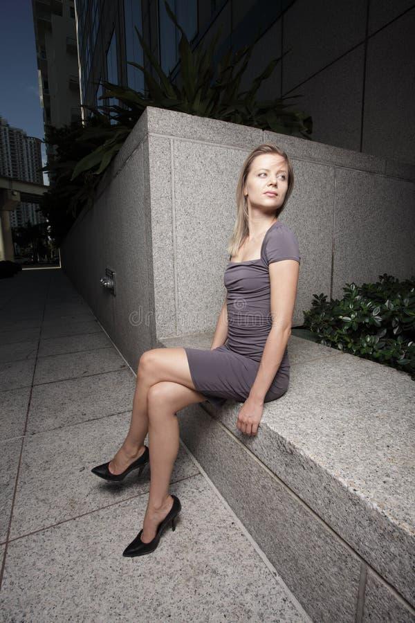 Mulher que senta-se com os pés cruzados fotografia de stock royalty free