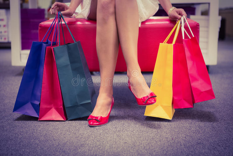 Mulher que senta-se com os pés cruzados e que guarda sacos de compras fotos de stock royalty free