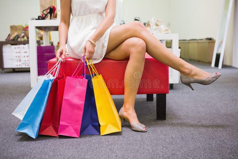 Mulher que senta-se com os pés cruzados e que guarda sacos de compras imagens de stock