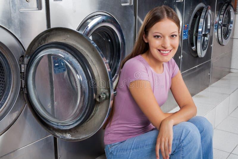 Mulher que senta-se contra máquinas de lavar fotografia de stock