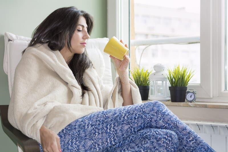 Mulher que senta-se em casa, envolvido em uma cobertura, chá bebendo imagem de stock royalty free