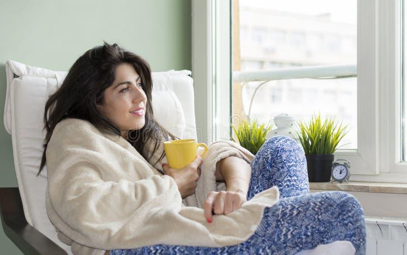 Mulher que senta-se em casa, envolvido em uma cobertura, chá bebendo imagem de stock