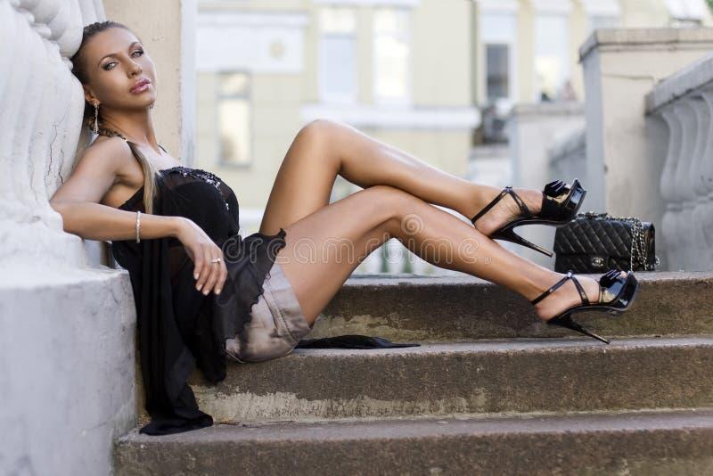 Mulher que senta-se em etapas da escada foto de stock