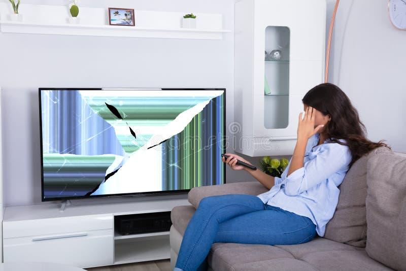 Mulher que senta-se em Sofa With Broken Television fotografia de stock