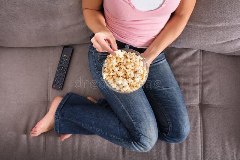 Mulher que senta-se em Sofa Eating Popcorn fotos de stock royalty free