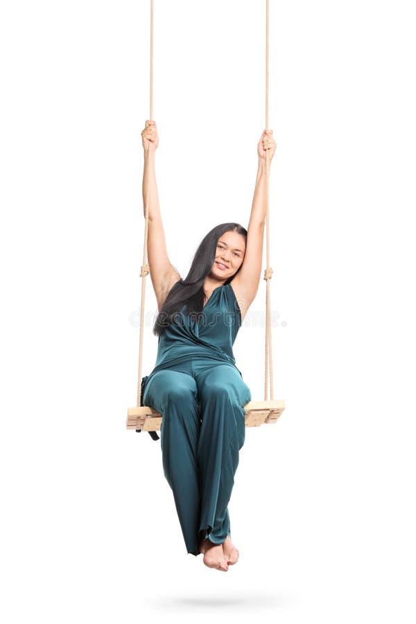 Mulher que senta-se em um balanço de madeira imagem de stock royalty free