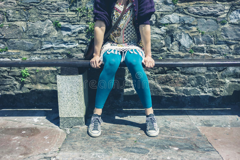 Mulher que senta-se em um banco fora imagens de stock