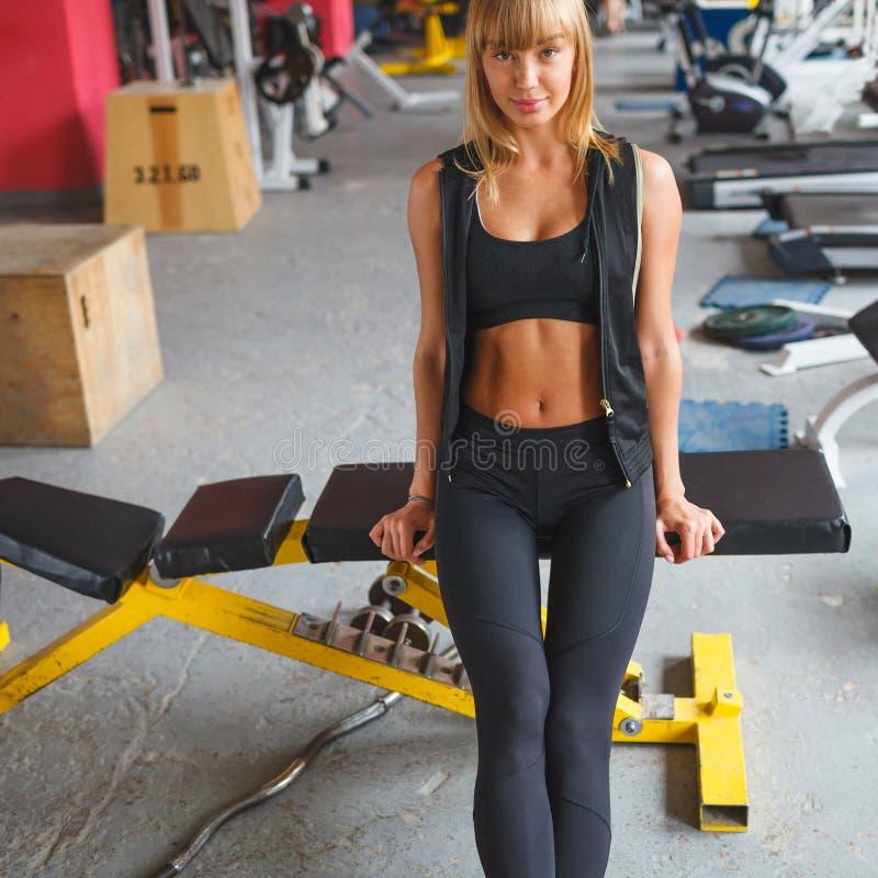 Mulher que senta-se em um banco no gym imagem de stock