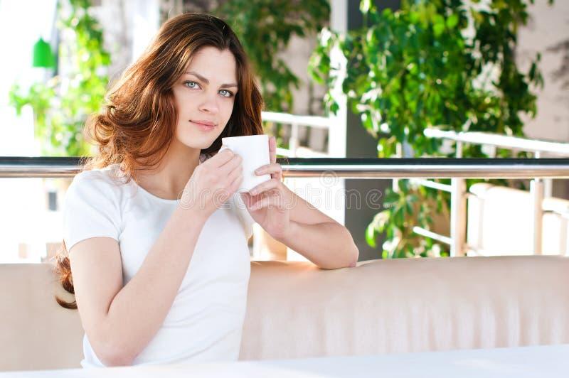 Mulher que senta-se em um café com um coffe imagem de stock royalty free