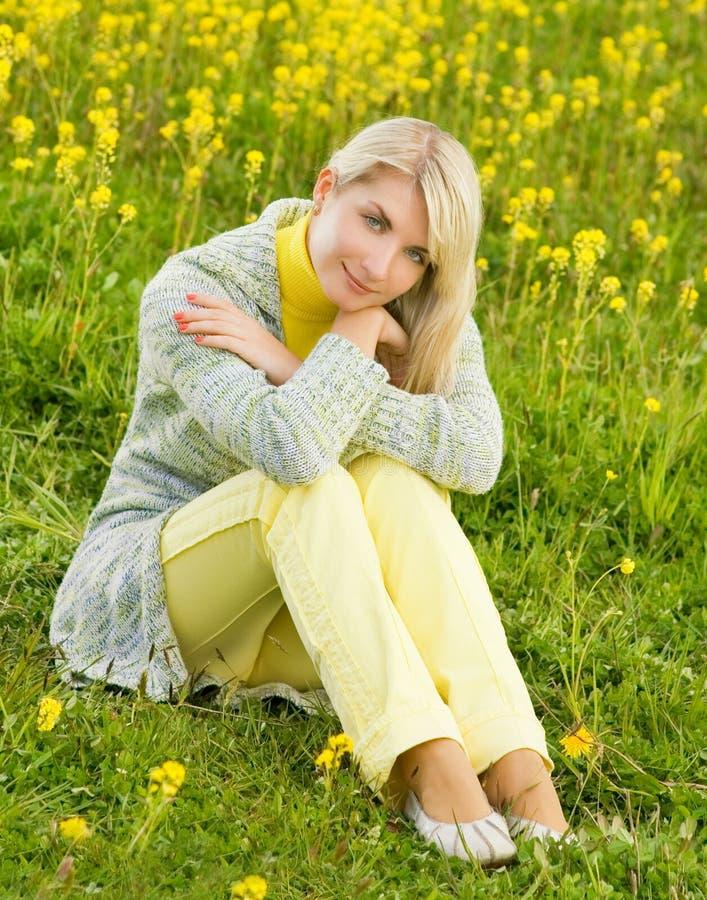 Mulher que senta-se em um campo de flor fotografia de stock royalty free