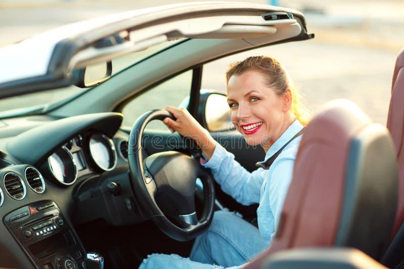 Mulher que senta-se em um conceito automobilístico convertível de comprar um Ca usado imagem de stock royalty free