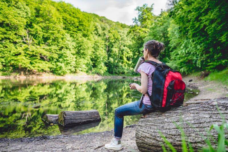 Mulher que senta-se em um log da árvore pelo lago foto de stock royalty free