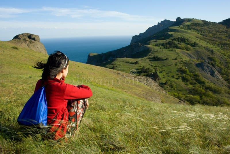 Mulher que senta-se em um monte e que olha ao mar foto de stock