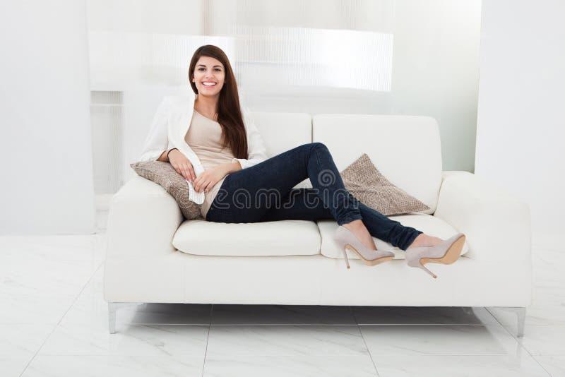Mulher que senta-se em um sofá fotos de stock royalty free