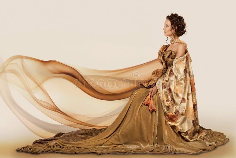Mulher que senta-se em um vestido foto de stock royalty free
