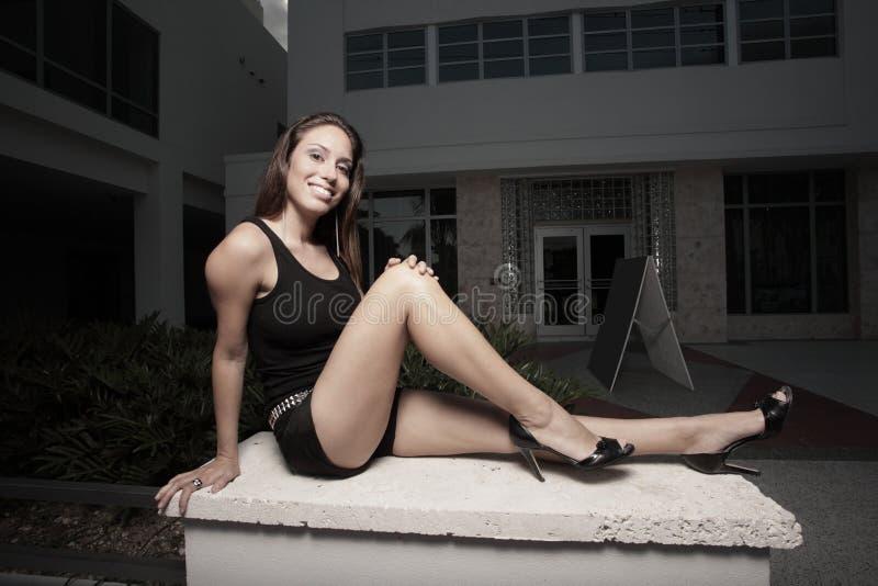 Mulher que senta-se em uma borda imagem de stock royalty free