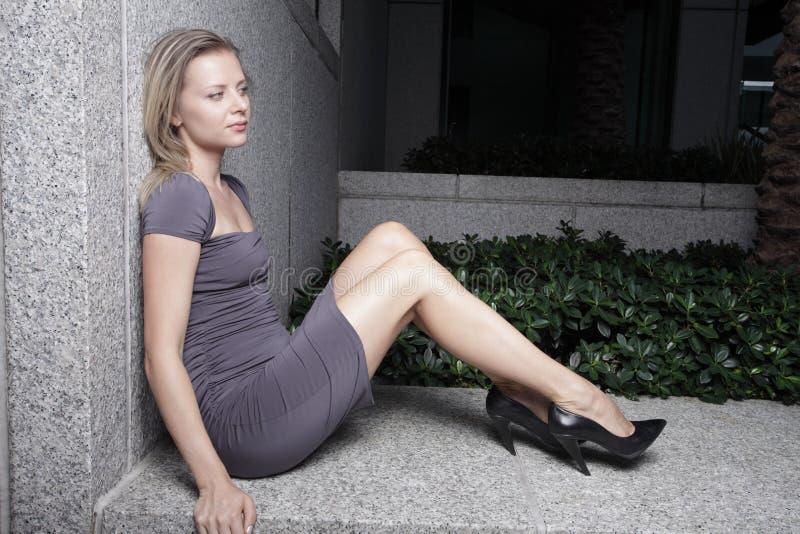 Mulher que senta-se em uma borda imagens de stock royalty free