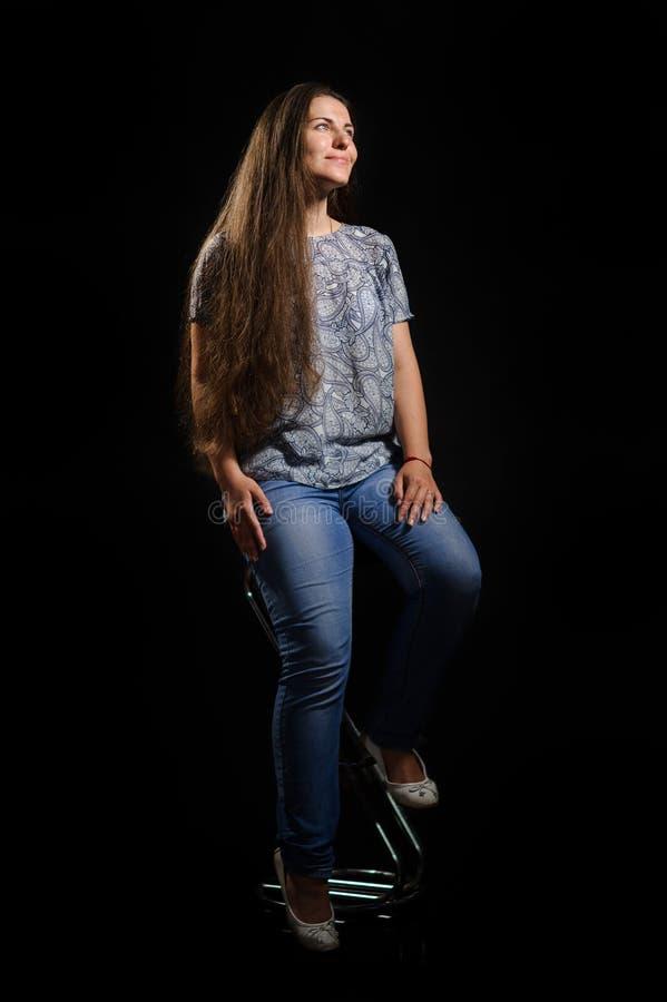 Mulher que senta-se em uma cadeira Imagem do estúdio, fundo preto fotografia de stock