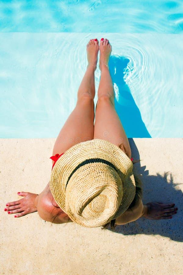 Mulher que senta-se em uma piscina