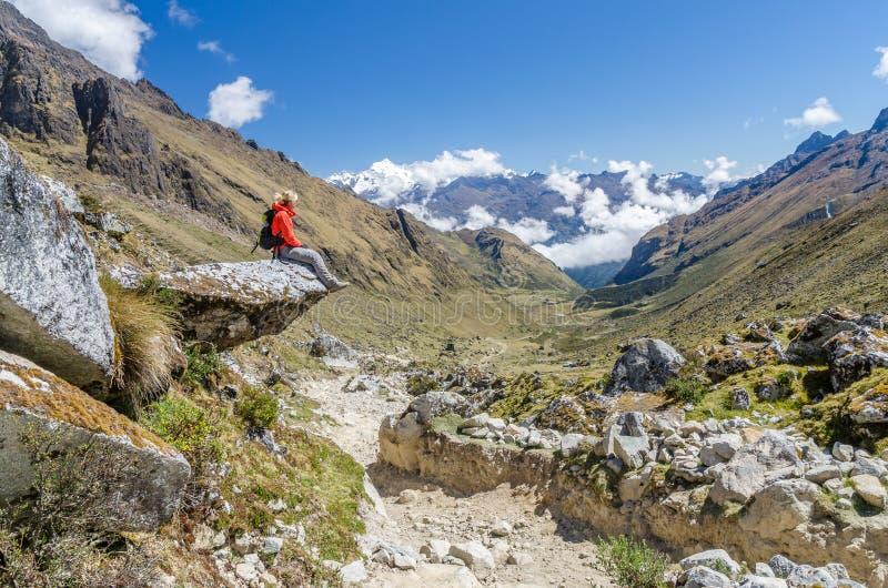 Mulher que senta-se em uma rocha durante o passeio na montanha de Salkantay imagens de stock