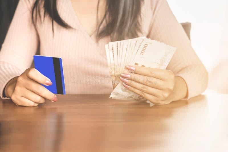 Mulher que senta-se em uma tabela que escolhe entre o cartão de crédito e as cédulas para o pagamento fotos de stock