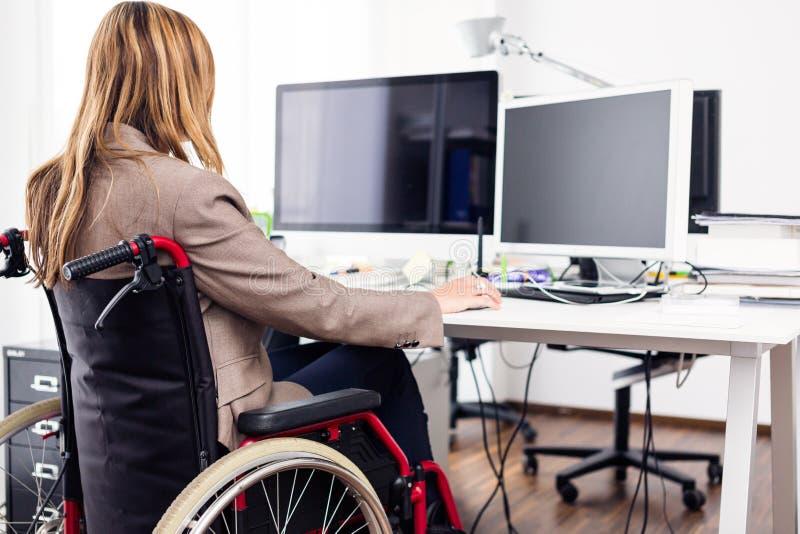 Mulher que senta-se na cadeira de rodas que trabalha no escritório moderno imagem de stock