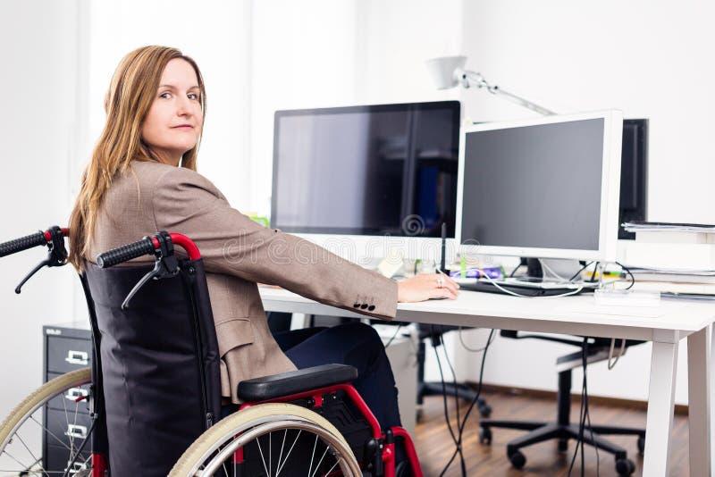 Mulher que senta-se na cadeira de rodas que trabalha no escritório moderno fotografia de stock