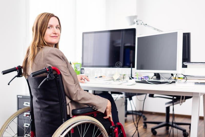 Mulher que senta-se na cadeira de rodas que trabalha no escritório moderno imagem de stock royalty free