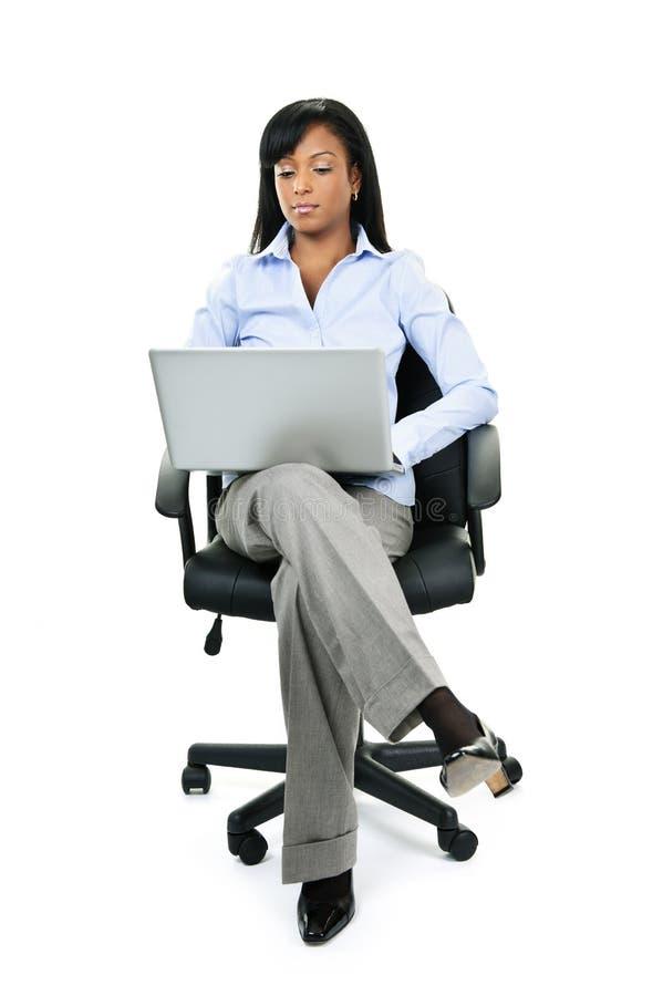 Mulher que senta-se na cadeira do escritório com computador foto de stock royalty free