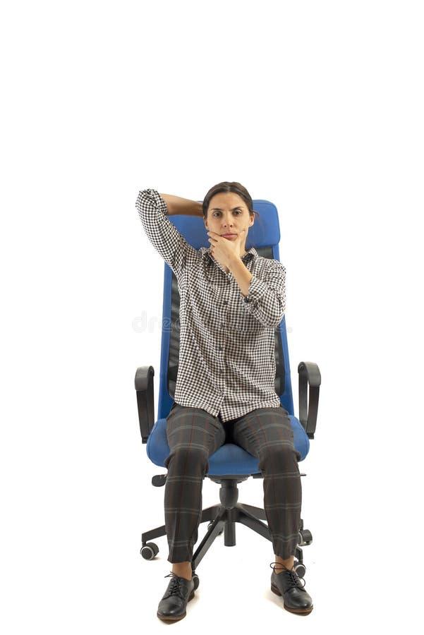 Mulher que senta-se na cadeira do escritório e que move sua cabeça fotos de stock