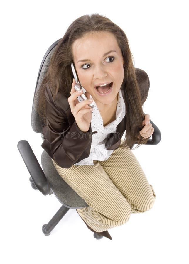 Mulher que senta-se na cadeira do escritório - falando ao telefone móvel fotografia de stock