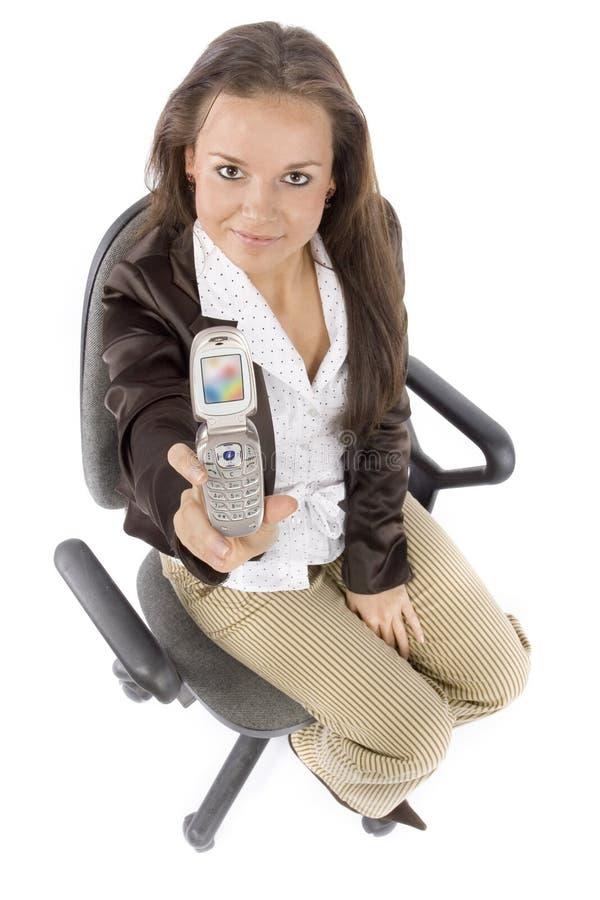 Mulher que senta-se na cadeira do escritório - mostrando a tela do móbil imagens de stock royalty free